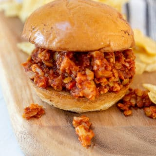A wooden board with a sloppy Joe sandwich and potato chips.
