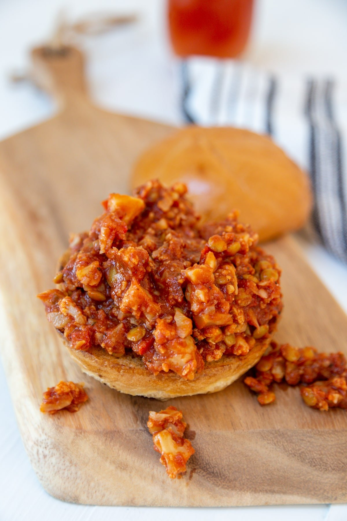 A pile of sloppy Joes on the bottom of a bun with the top of the bun next to it.