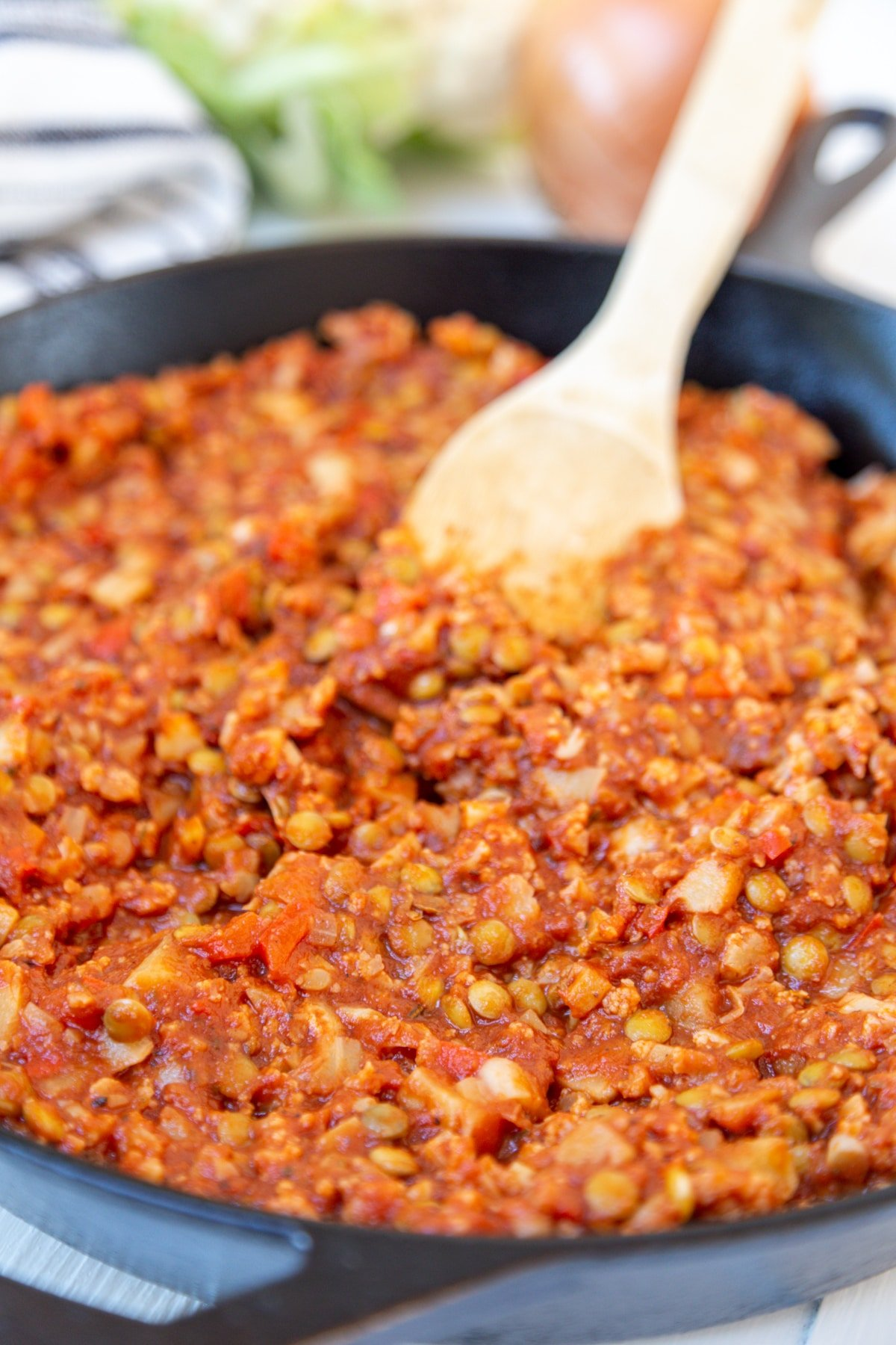 An iron skillet with sloppy Joes being stirred with a wooden spoon.