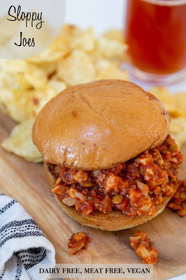 A Pinterest pin for vegan sloppy Joes with a picture of a sloppy Joe sandwich on a wooden board with potato chips and a glass of beer.