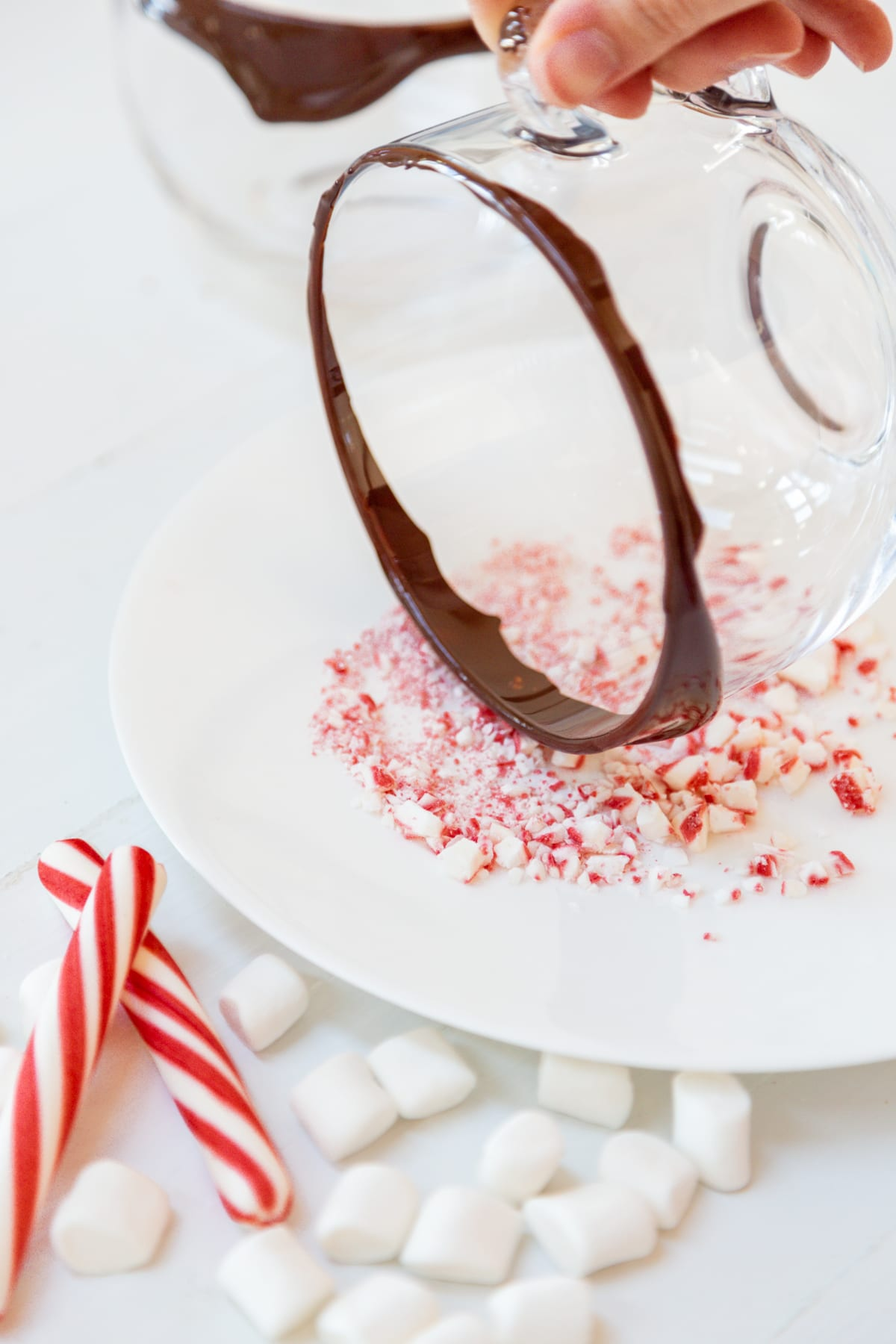 A clear glass mug rimmed with chocolate being dipped into crushed peppermint candy.