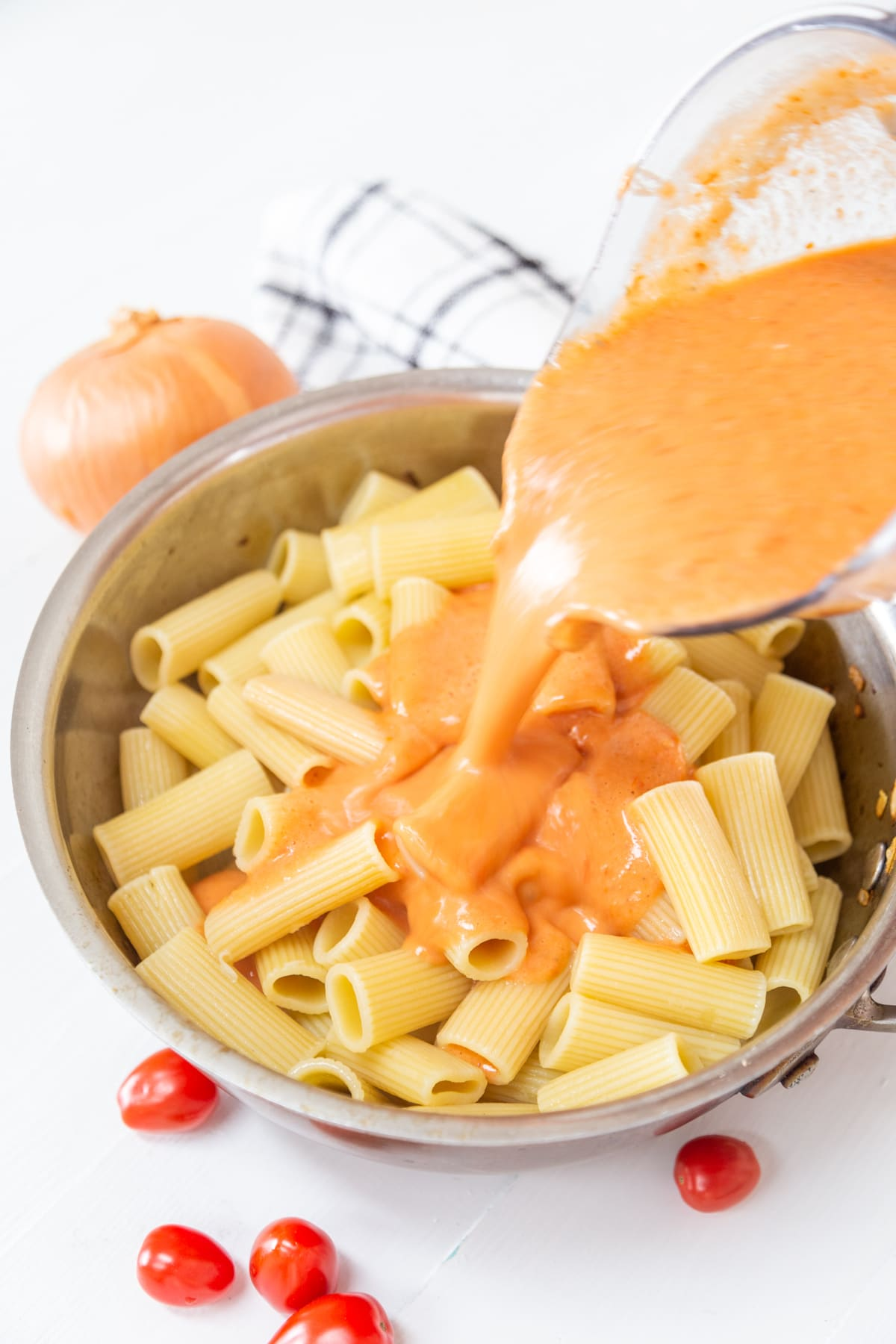 A pan with rigatoni and a pitcher of vodka sauce being poured over the pasta.