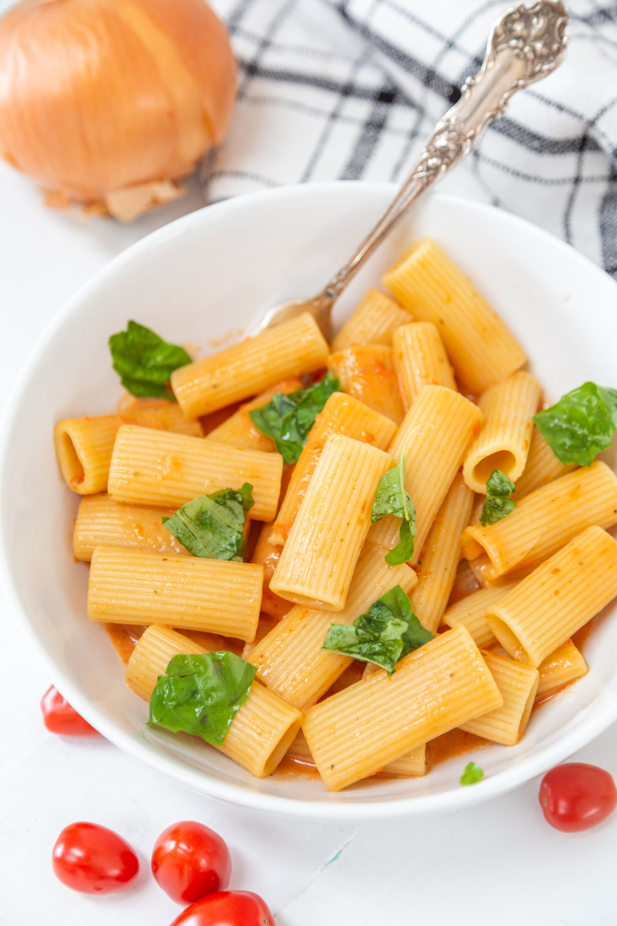 A white bowl with rigatoni and creamy red sauce, with cherry tomatoes and an onion next to the bowl.