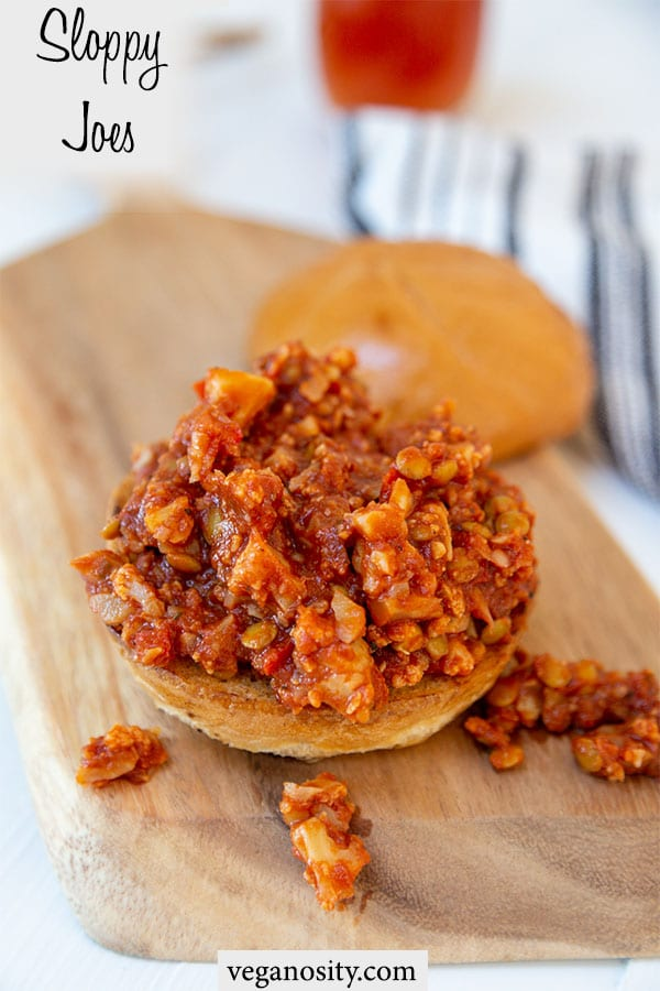 A Pinterest pin for vegan sloppy Joes with a picture of an open face sloppy Joe sandwich on a wooden board.