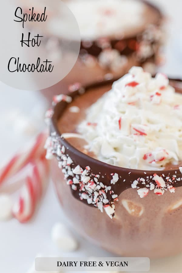 A Pinterest pin for spiked peppermint hot chocolate with a mug of the hot chocolate with whipped cream and a peppermint stick.