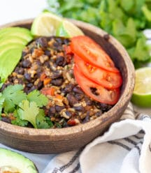 A brown wood bowl with black beans and rice with vegetables and an avocado and cilantro around the bowl.