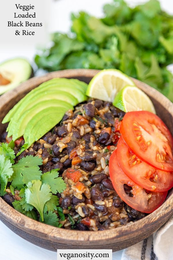 A Pinterest pin for black beans and rice with a picture of the rice and beans with avocado and tomato slices in a wooden bowl.