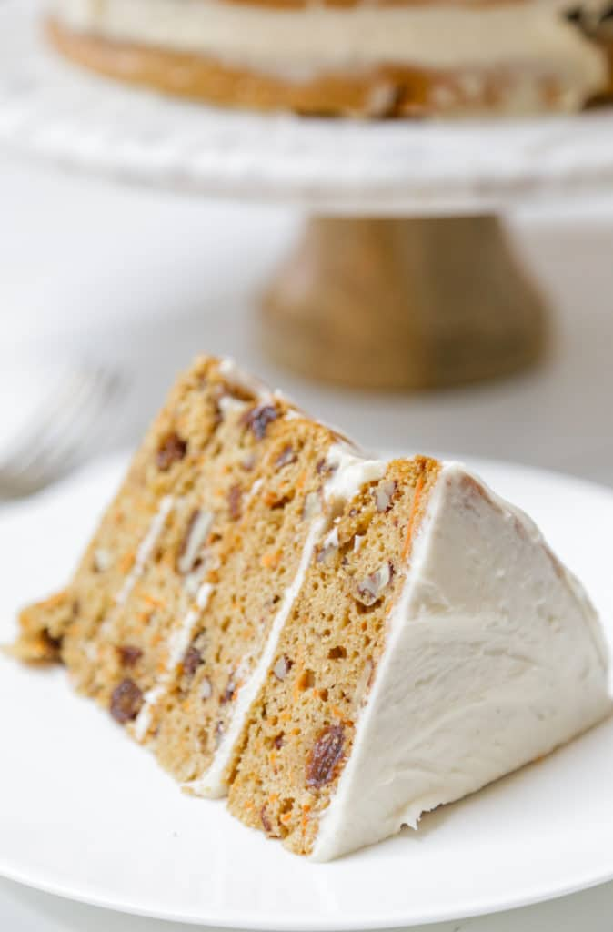 A 4 tiered slice of frosted carrot cake on a white plate with the whole cake in the background.