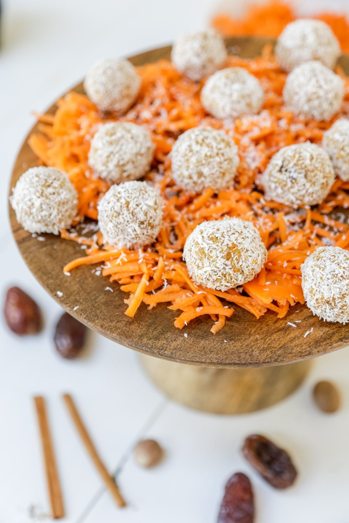 Carrot cake balls rolled in coconut sitting on grated carrots on a wooden cake stand.