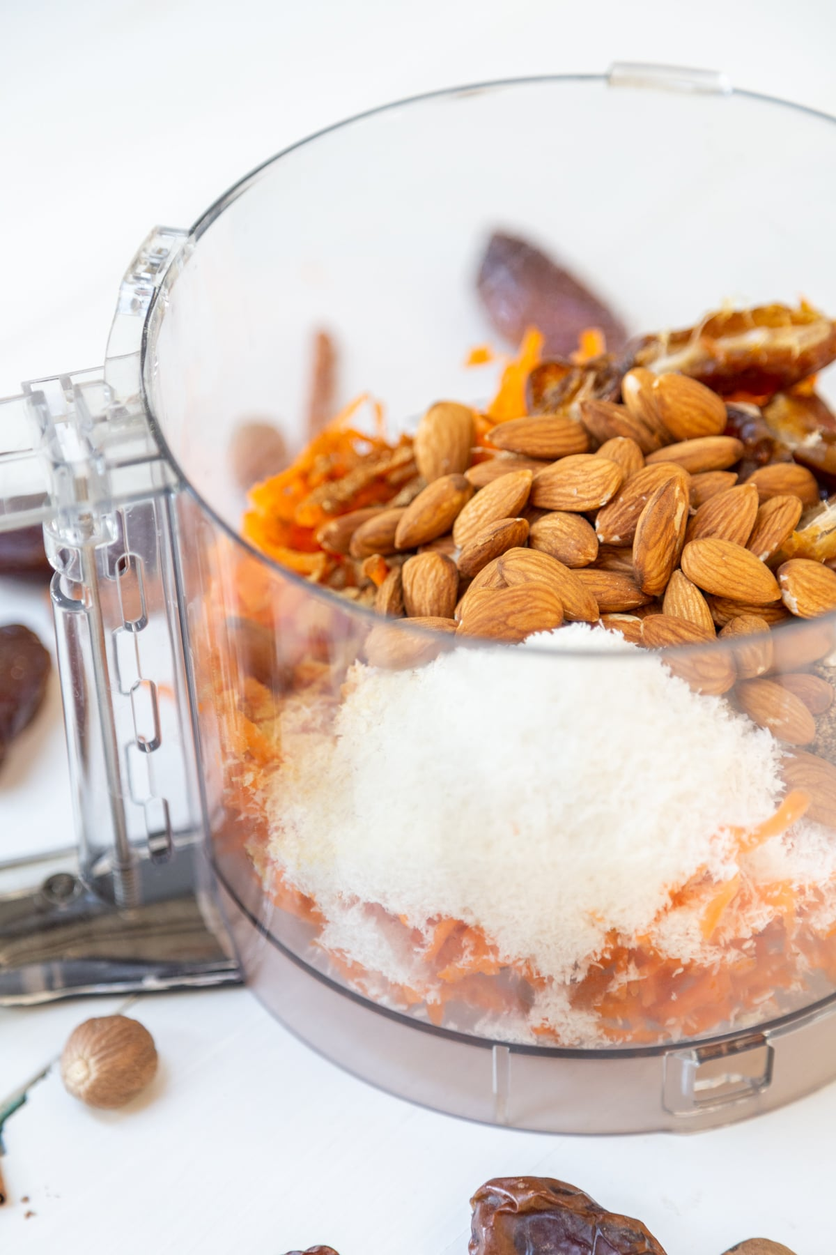 A food processor filled with almonds, dates, shredded coconut and carrots.