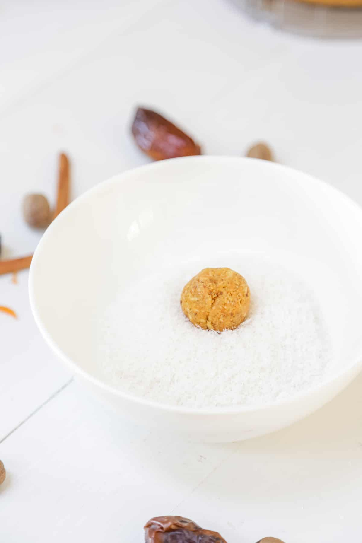 A carrot cake ball in a white bowl with shredded coconut.
