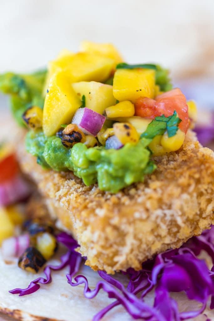 A close-up shot of a breaded tofu taco with avocado and mango salsa.