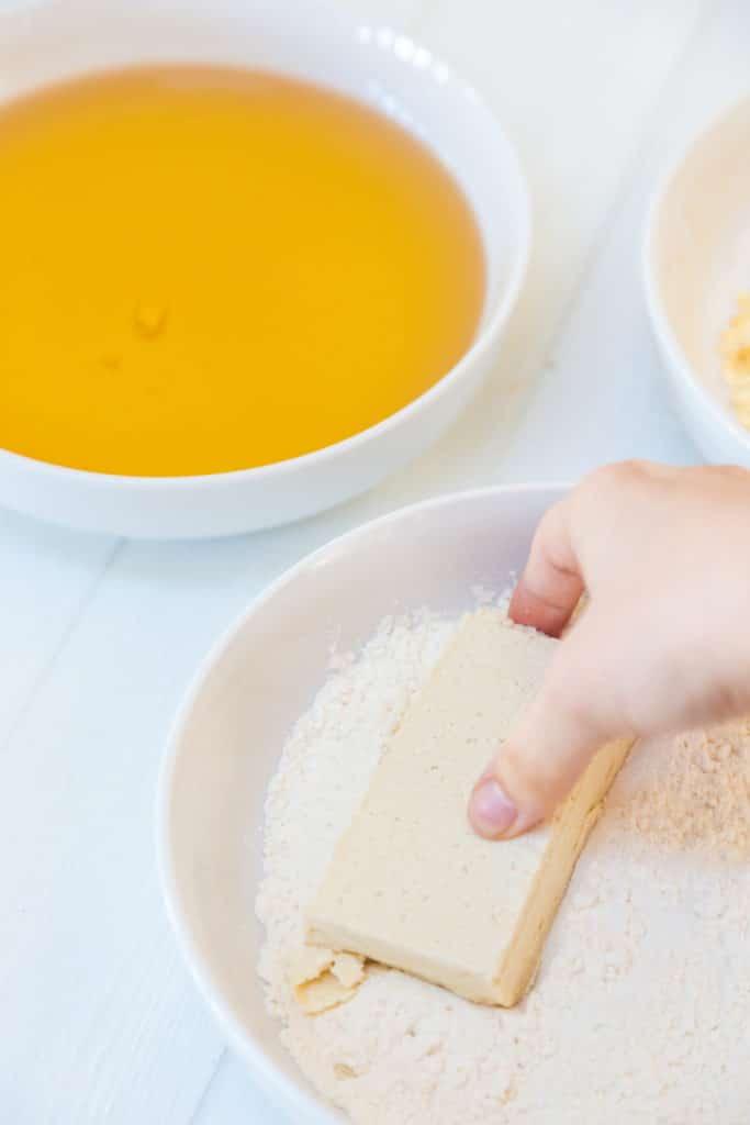 A hand dredging a slice of tofu through flour.