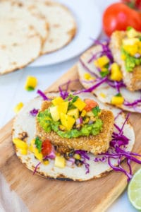 Breaded tofu tacos with mango salsa on a wooden board with flour tortillas in the background.