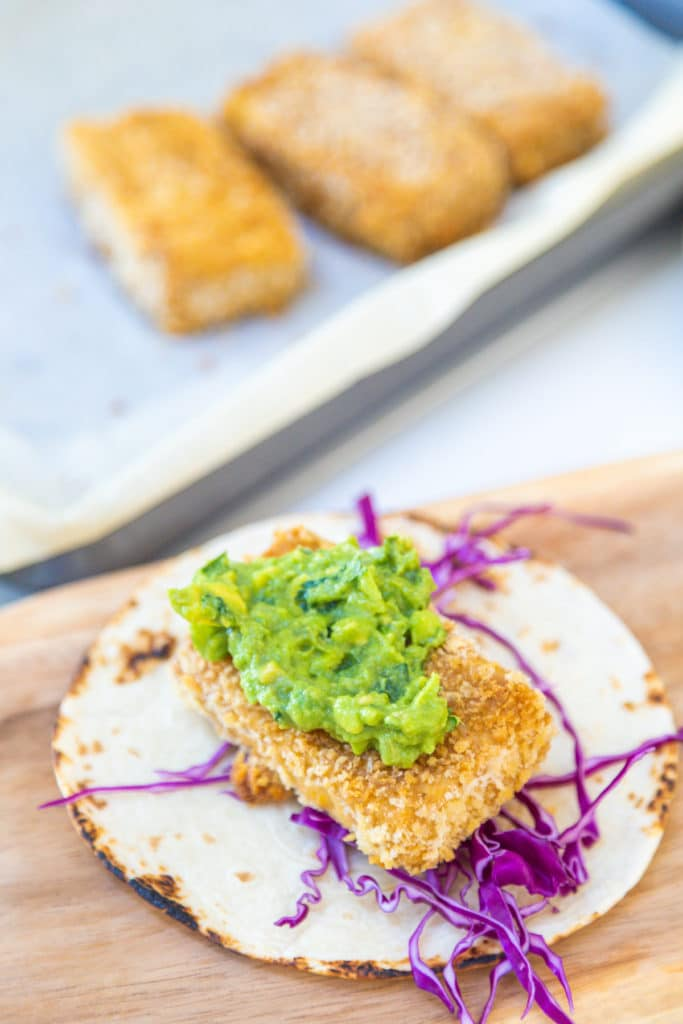 A tortilla with shredded cabbage, a breaded fried tofu stick, and mashed avocado.
