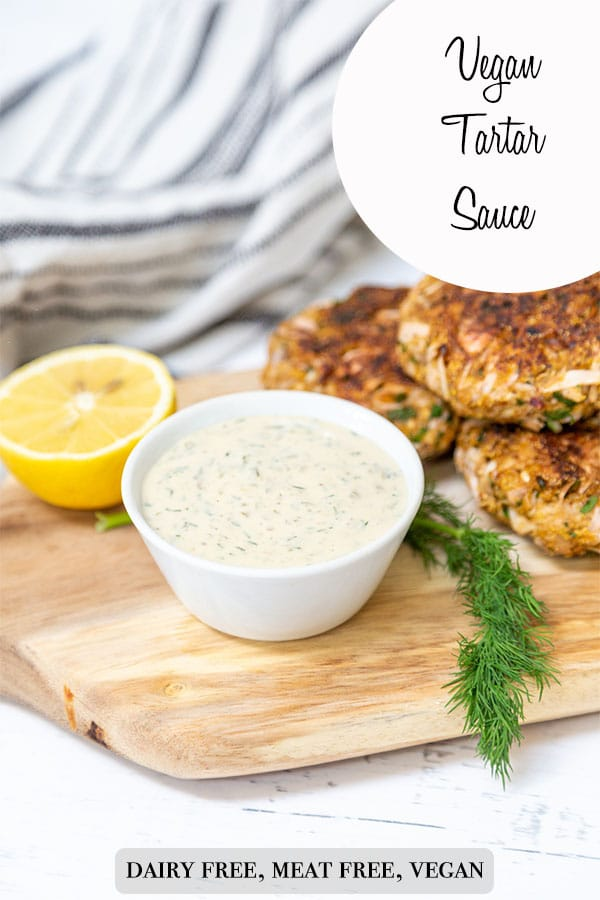 A Pinterest pin for vegan tartar sauce with a picture of the sauce in a white bowl on a wood board with crab cakes and fresh dill.